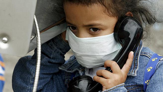 Una niña con mascarilla habla por teléfono en San José de Costa Rica.