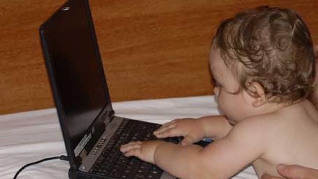 Un bebé juega con un ordenador portátil.