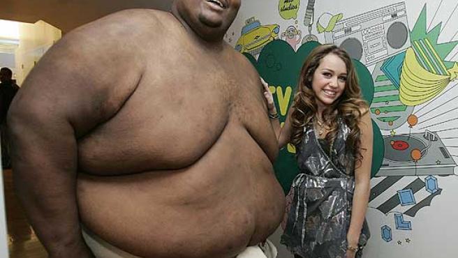Miley Cyrus posa junto al luchador de sumo Manny Yarbrough.