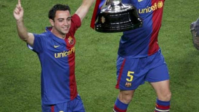 Los capitanes del FC Barcelona Carles Puyol (d) y Xavi Hernández (i) alzan la copa que acredita a su equipo como campeón de Liga 2008/2009.
