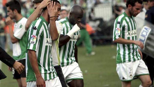 El brasileño Oliveira, el camerunes Emana y Fernando Vega, del Real Betis, se retiran confirmarse que el equipo desciende a segunda división.