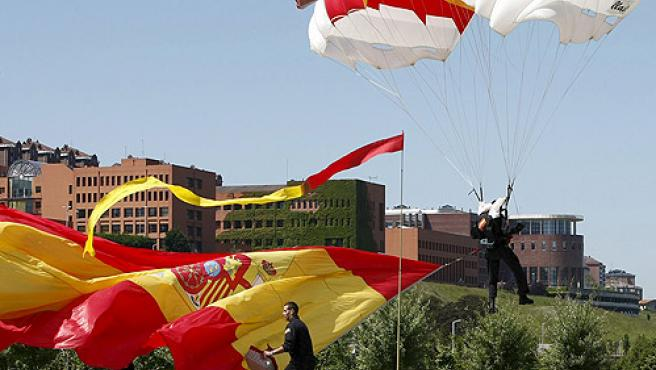 Llegada de la bandera española portada por un paracaidista, durante la celebración en Santander del Día de las Fuerzas Armadas.