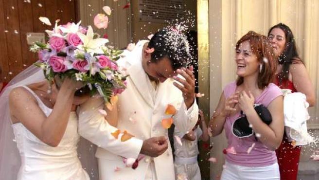 Una pareja de recién casados sale de la iglesia tras haber contraído matrimonio.