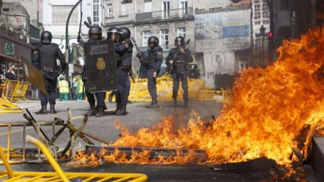 Varios miembros de la Policía Nacional junto a barricadas con fuego, durante las movilizaciones del metal en Vigo.