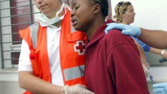 Un miembro de la Cruz Roja acompaña a uno de los 22 inmigrantes subsaharianos rescatados.