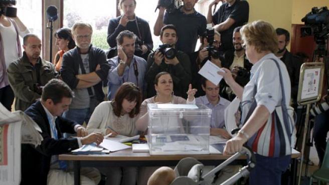 Una mujer, acompañada de un bebé en su carrito, ejerce su derecho al voto para las elecciones al Parlamento Europeo.