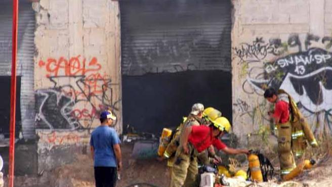 Miembros del cuerpo de bomberos trabajan en la fábrica de neumáticos que se incendió.
