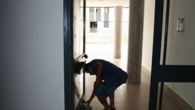 Un vecino coloca un papel para que sujete la puerta y así la luz pueda entrar en el edificio.