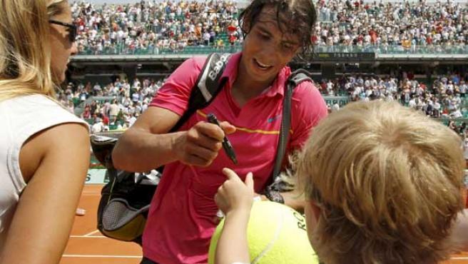 El tenista español Rafa Nadal firma autógrafos a pie de pista al término de un partido de Roland Garros.