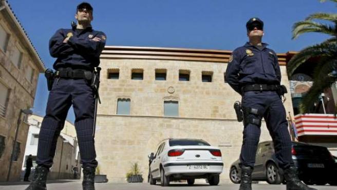Dos policías custodian el Ayuntamiento de La Muela durante el registro.