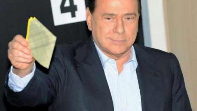 El primer ministro italiano, Silvio Berlusconi, vota en Milán este domingo.