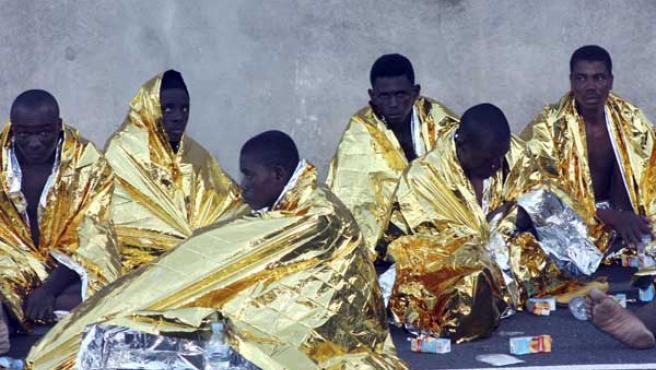 Varios inmigrantes descansan tras arribar en un cayuco a San Sebastián de la Gomera (EFE).