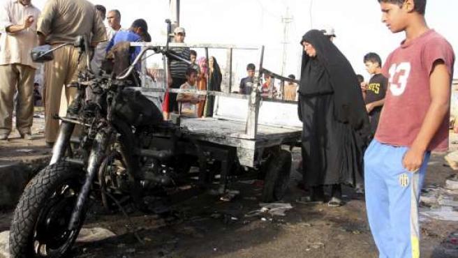 Varias personas observan los destrozos causados por la bomba en Ciudad Sadr en Bagdad.