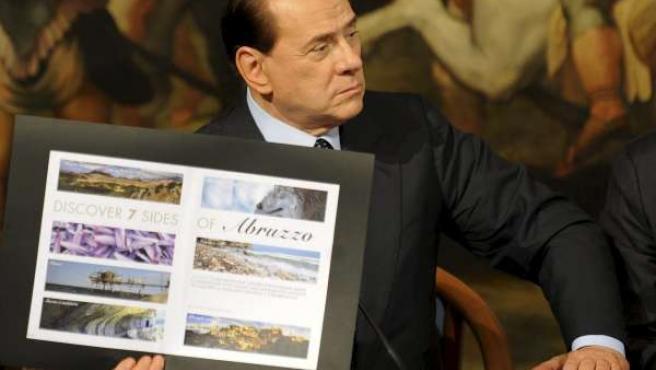 Silvio Berlusconi con una imagen de los Abruzzos.