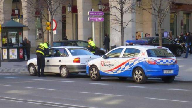 Dos policías ponen una multa a un conductor en el paseo de la Independencia.