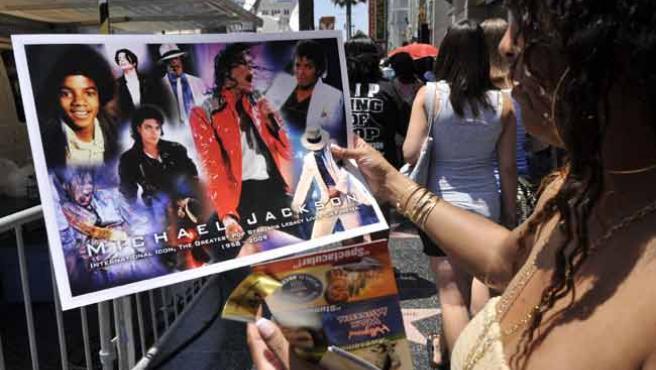 Una admiradora observa un poster de Michael Jackson, este sábado, en el Paseo de la Fama de Hollywood.