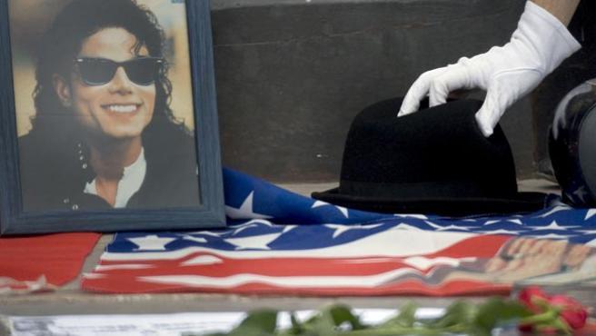 Un admirador de Michael Jackson deposita un sombrero junto a su foto en la plaza del Ayuntamiento de Valencia.