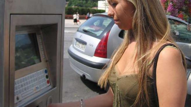 Una joven saca el tique de la OTA en Bilbao.