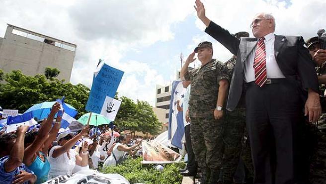 El nuevo presidente de Honduras, Roberto Micheletti, saluda a sus seguidores en la plaza central de Tegucigalpa.