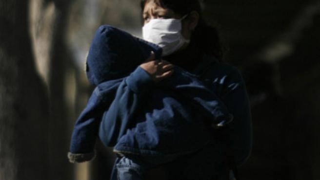 Una mujer con una máscara camina mientras protege a un niño en las afueras de un hospital de Buenos Aires.
