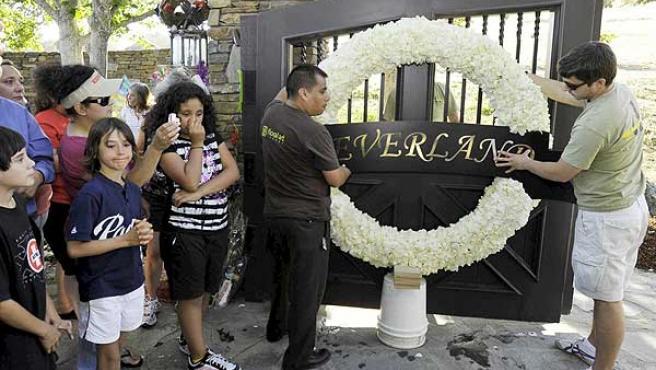 Unos operarios colocan coronas de flores a las puertas del rancho de Neverland.