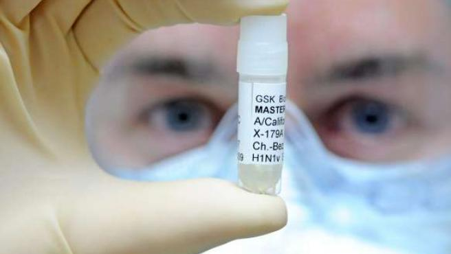 Un empleado de la farmacéutica 'GlaxoSmithKline' presenta una muestra del virus de la Gripe A.