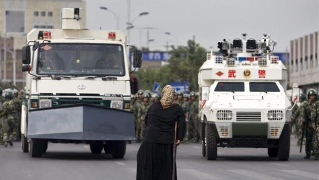 Una mujer uigur, delante de dos vehículos militares en Urumqi (Xinjiang, China), durante las protestas.