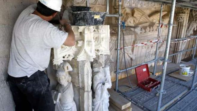 Un restaurador trabaja en las piezas nuevas que se pondrán en la fachada.