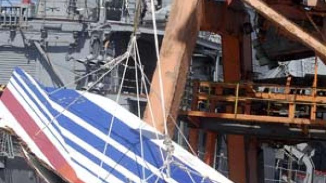Restos de la cola del avión siendo descargados en el puerto de Recife.