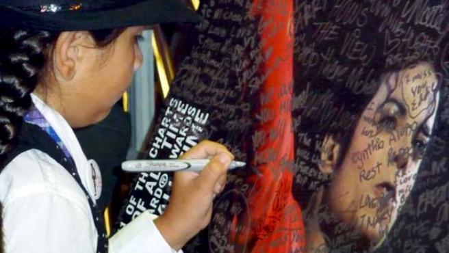 Una niña firma un cartel con la estampa de Michael Jackson.