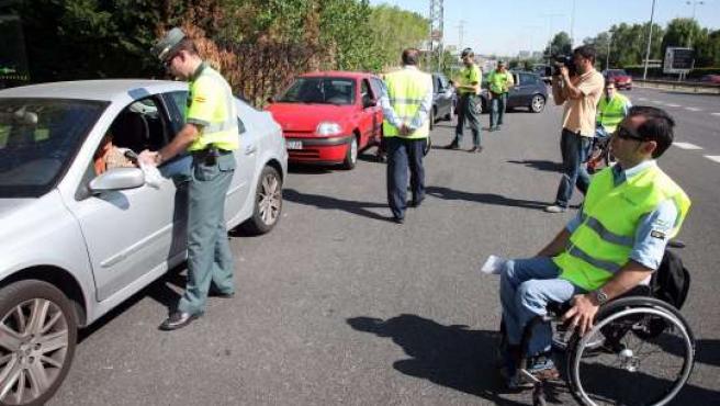Voluntarios de Aspaym explican su situación a los conductores.