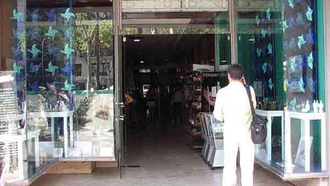 Un hombre habla por telefono delante de una tienda del centro de Barcelona sin luz en su interior. (ACN)