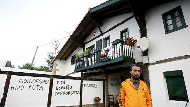 Zigor Goikoetxea, delante de las pintadas que unos desconocidos han hecho en la casa de sus padres.