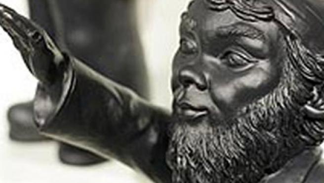 Una de las figuras de gnomo del artista con el brazo levantado.