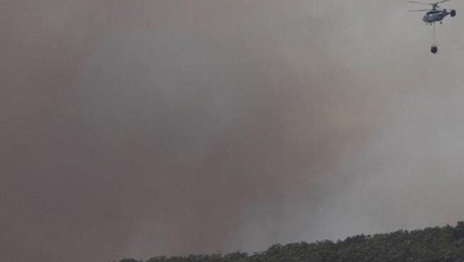 Un helicóptero sobrevuela en tareas de extinción el incendio de Tarifa.