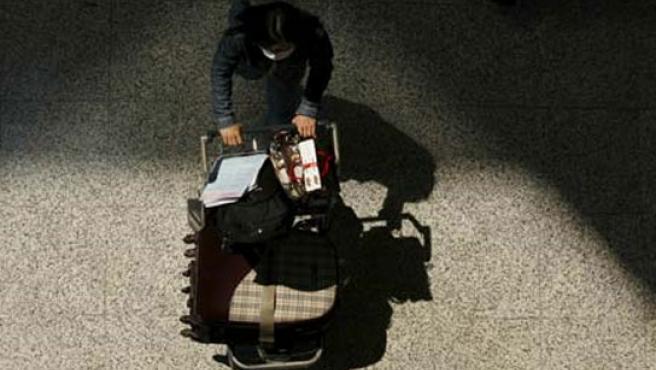 Un pasajero tomando medidas de precaución por la gripe A a la llegada al aeropuerto.