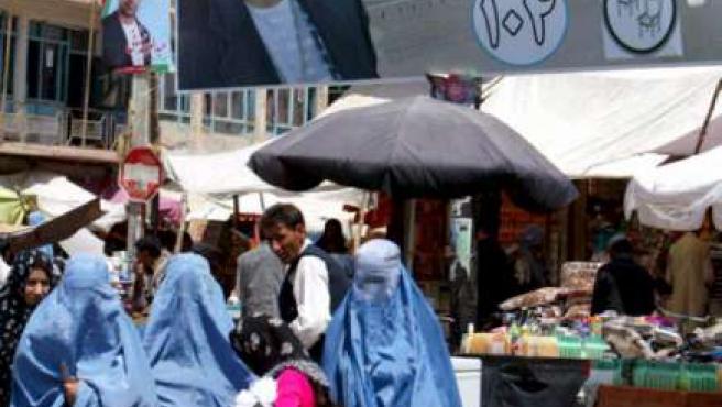 Mujeres afganas ataviadas con el burka caminan junto a un cartel con la imagen del candidato provincial Haji Hamed Javed.