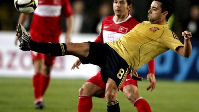Xavi Hernández intenta controlar el balón ante Emre.