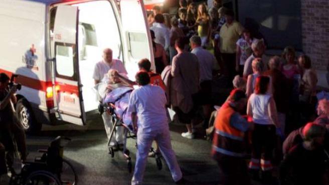 Los sanitarios trasladan a ancianos afectados por el incendio de su residencia en Bélgica.