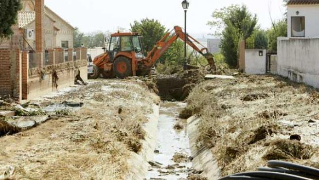 Una máquina excavadora trabaja tras las inundaciones en Toledo.