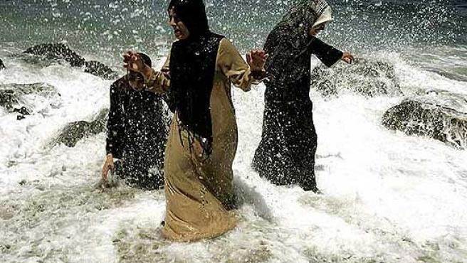 Tres mujeres se bañan en el mar, en Argelia.