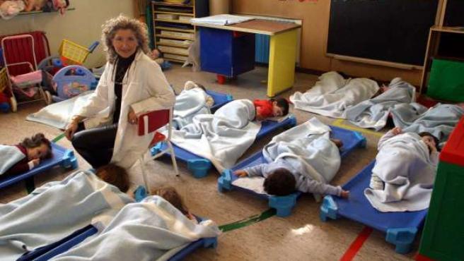 Un grupo de niños duermen la siesta en una guardería.