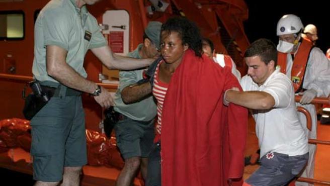 Guardia Civil y Cruz Roja atienden a uno de los 35 inmigrantes subsaharianos que han llegado esta madrugada al puerto de Motril.