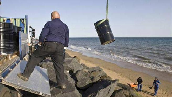 Operarios de la refineria CEPSA-La Rabida descargan bidones en una de las playas de Doñana.