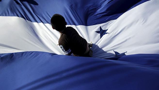 Un niño sobre una bandera de Honduras durante un mitin en apoyo a Roberto Micheletti en Tegucigalpa.
