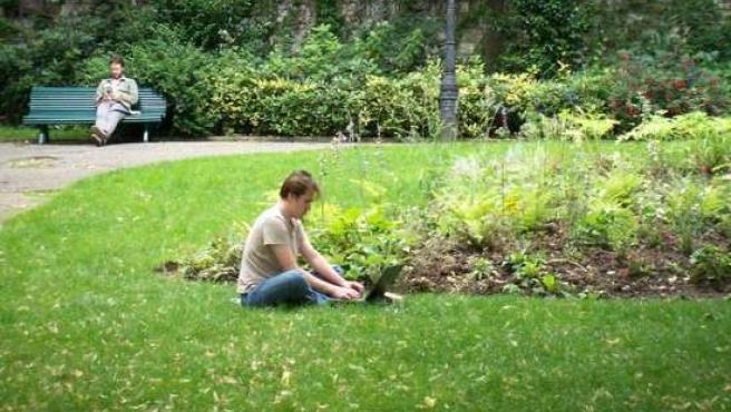 Un joven se conecta a internet en un parque.