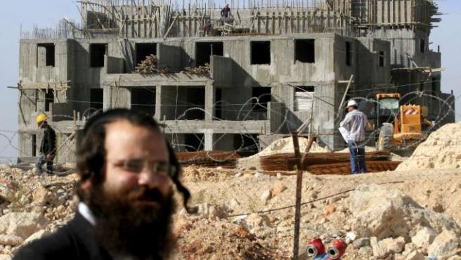 Un judío ultraortodoxo pasea por delante de unas casas en construcción en Cisjordania.