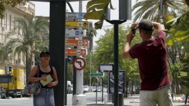 Una pareja de turistas se fotografía bajo un termómetro de ambiente que marca 45 grados centígrados.