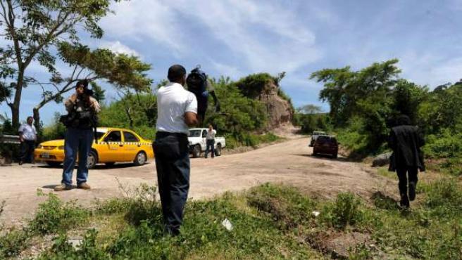Varios periodistas en la carretera salvadoreña en la que fue asesinado el fotógrafo español Christian Poveda.