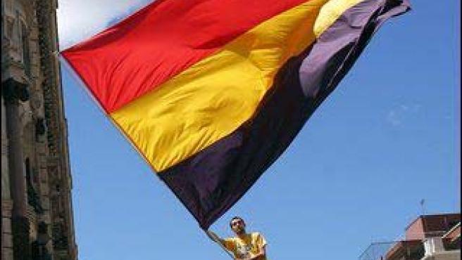 Jaume d'Urgell, ondeando la bandera republicana en la azotea de un edificio.